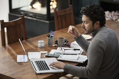 Man working on home finances at dining room table