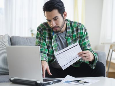 A man sitting on a sofa using a laptop on the coffee table as he sorts through a stack of bills and statements