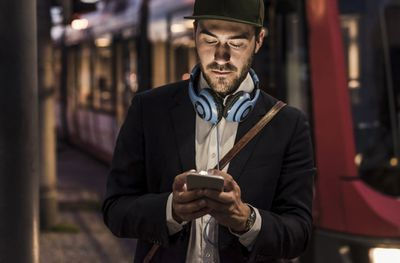 young person with hat on and headphones on neck, looking at something on his iPhone