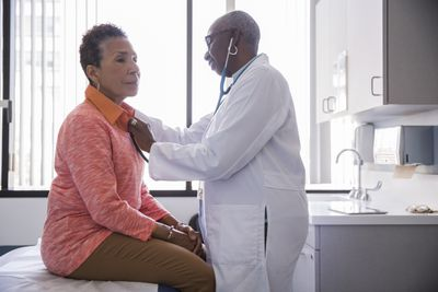 Female doctor uses stethoscope on mature female patient