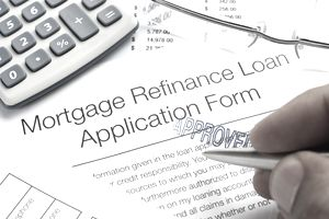 Approved Mortgage Refinance Application Form with pen, calculator