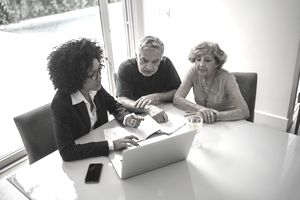 Businesswoman and older couple consult laptop and paperwork at home