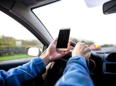 Man using smartphone whilst driving.