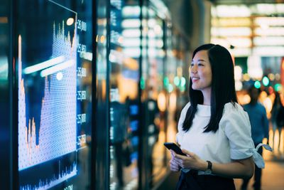 Woman watching a stock market graph for trading decisions