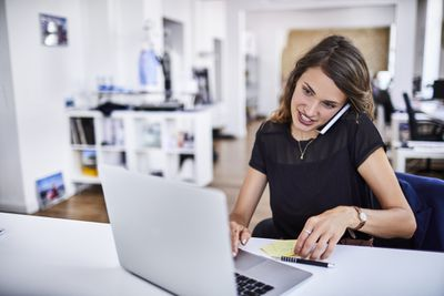 Woman talking on phone while working on laptop