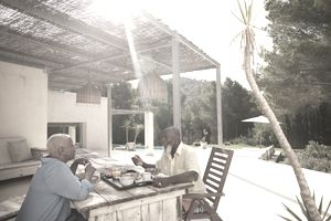 Couple eating breakfast outside on the deck with a pool and a beautiful landscape in the background