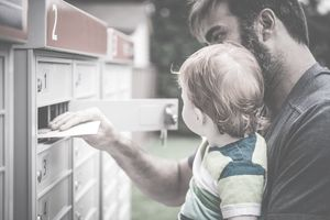 A man holding a toddler opens a mailbox and takes out letters.