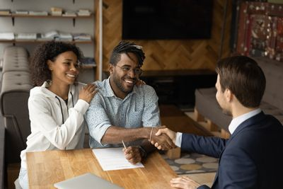 Smiling young couple shakes hands with businessman over paperwork