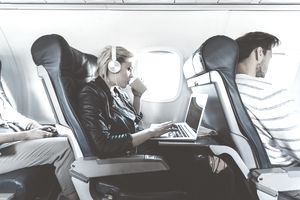 An airline passenger wearing headphones drinks coffee while working on a laptop