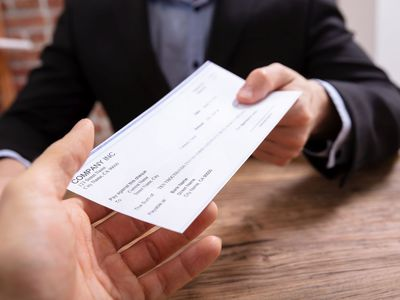 Hand of man in a dark suit handing a check to another person's open hand across a desk
