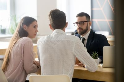 Broker listening to clients during office meeting or consultation