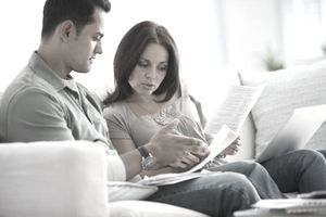 a couple going over financial documents while sitting on their couch.
