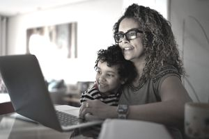 Woman in glasses uses laptop with young son in lap