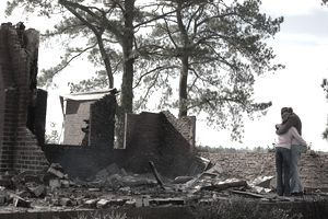 Two people embrace next to destroyed home after storm