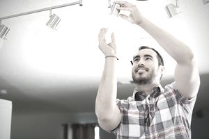Home seller fixing light fixture as requested in his home sale