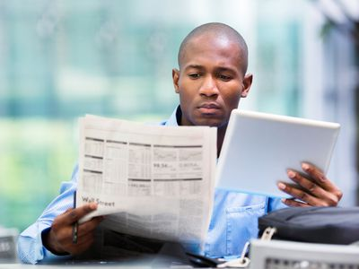 Investor compares stock quotes on tablet and newspaper