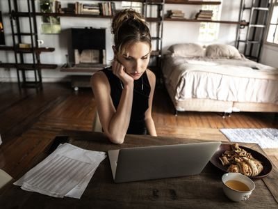 Woman working on laptop at home studio with pastries and coffee