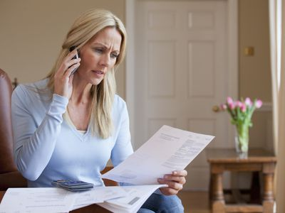 A woman looks at her deceased parent's debts while speaking on the phone with a probate attorney.