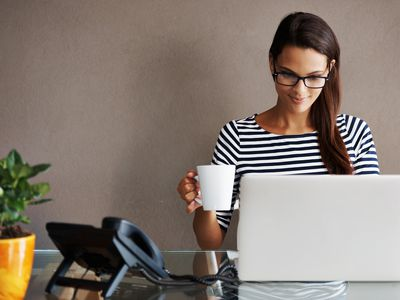 Shot of a beautiful young woman wearing glasses and typing on her laptop at home