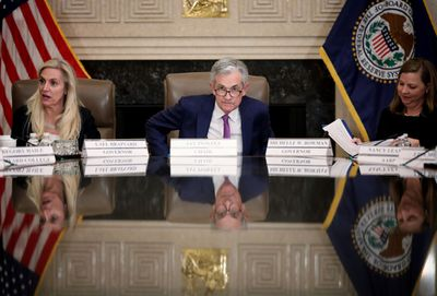 Fed chairman Jerome Powell sits at a table flanked by colleagues.