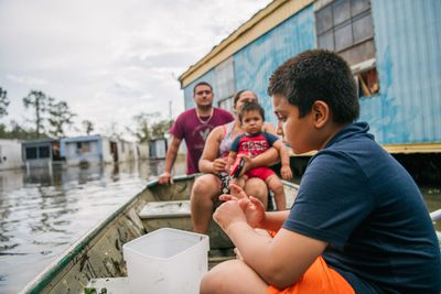 BARATARIA, LOUISIANA - AUGUST 31: The Maldonado travel by boat to their home after it flooded during Hurricane Ida on August 31, 2021 in Barataria, Louisiana.