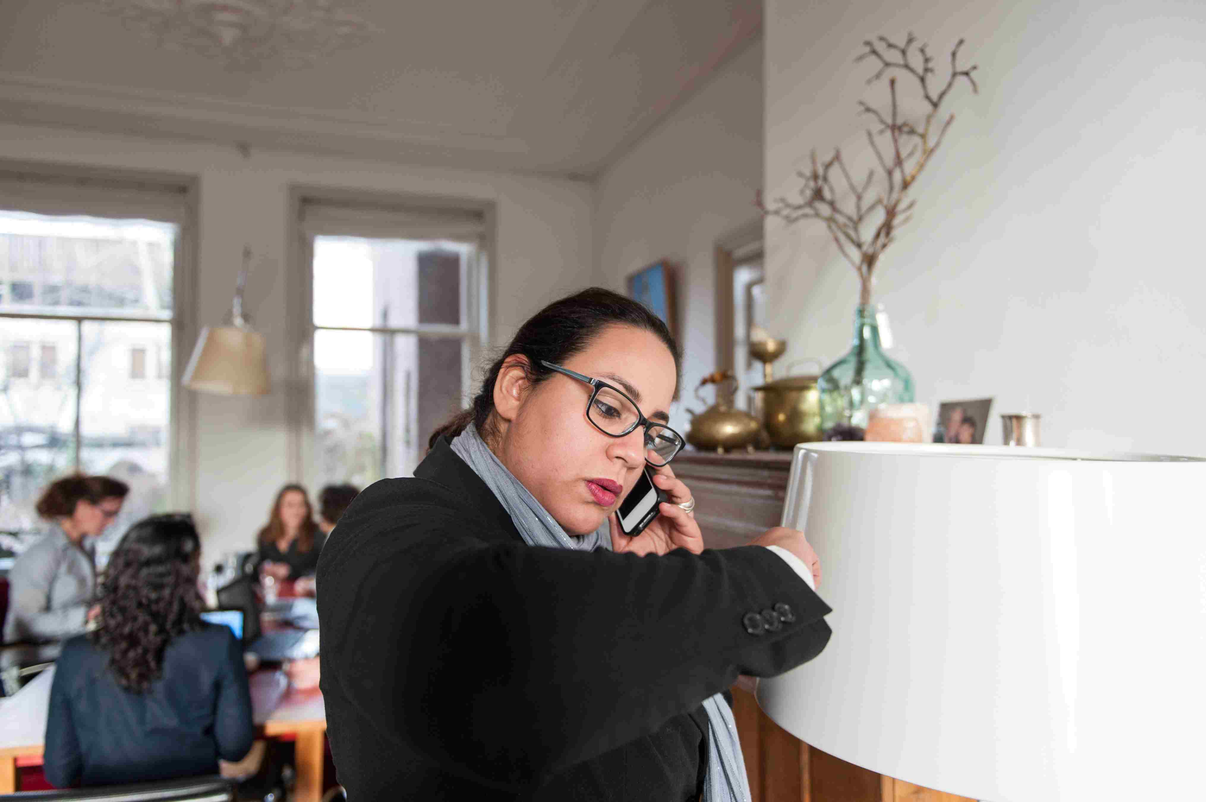 Business woman making phone call during a meeting