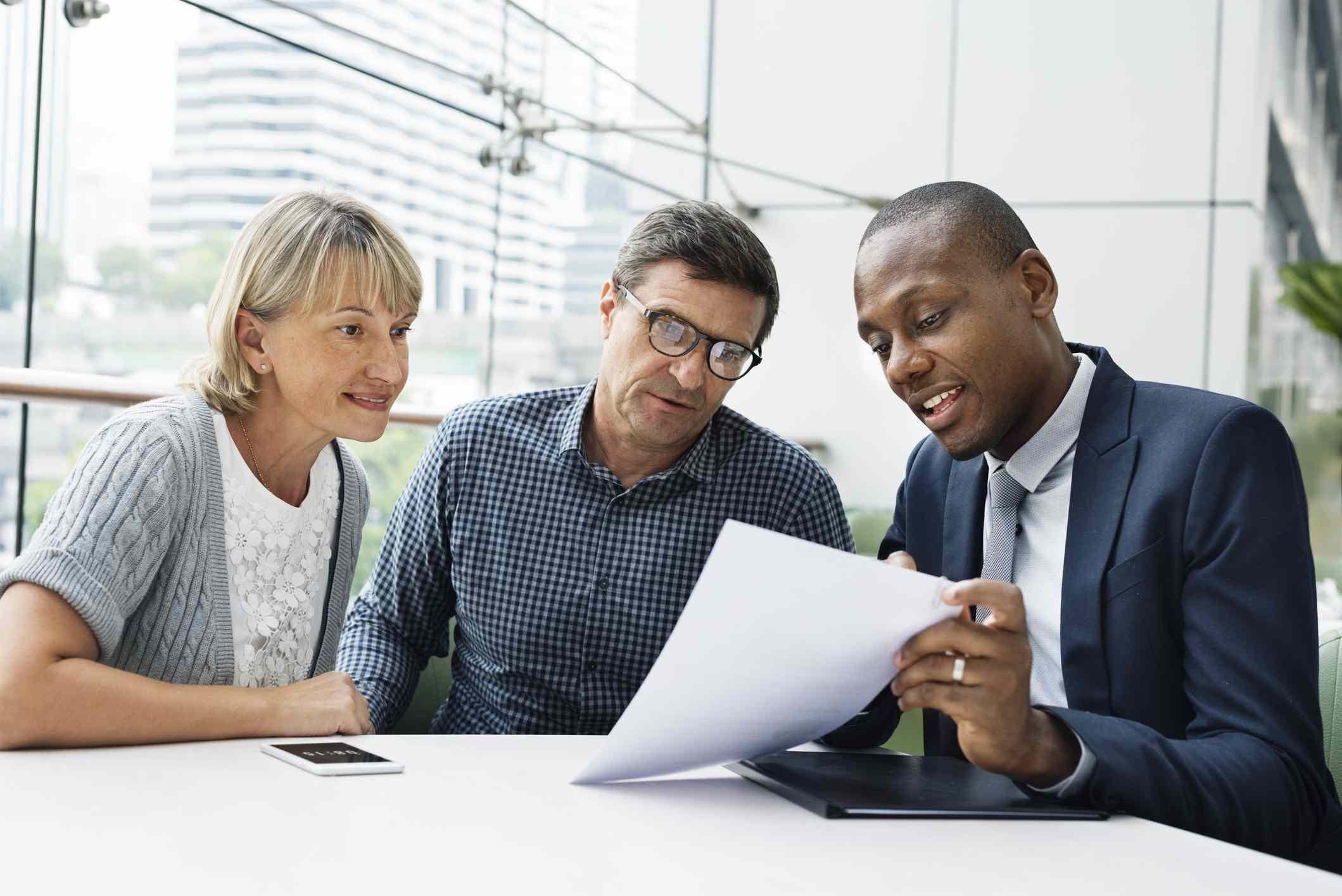 Male financial advisor showing middle-aged couple that tax rate is a factor when considering a Roth IRA