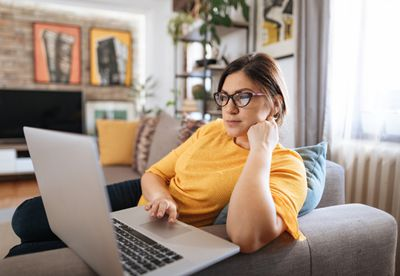 Woman working on laptop on couch at home