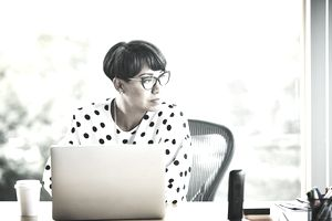 A woman wearing glasses and a polka-dot blouse looks off to the side while sitting at her laptop, considering insurance portability