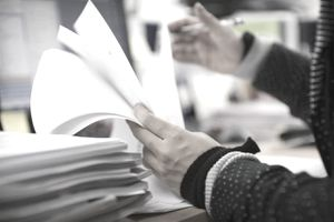 Closeup of hands checking documents on desk