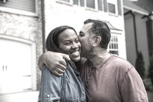 A couple embrace as they stand in front of their new home.