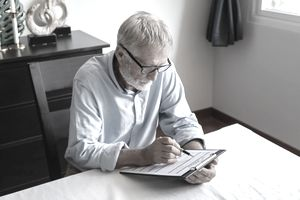 Gray-Haired Man in Blue Shirt Reviewing Application Form at Home Dining Table.