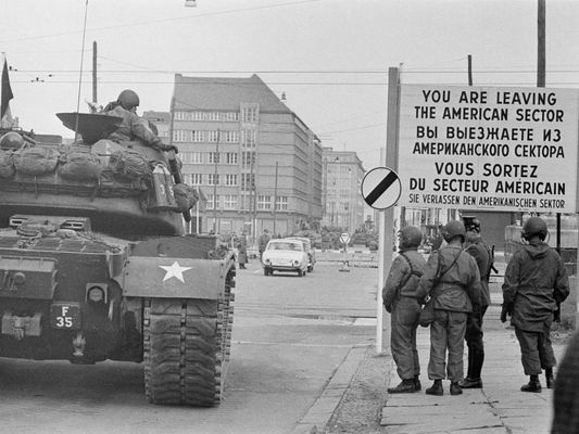 Black and White Photo of Tank Crossing Checkpoint Charlie Into East Berlin During Cold War.