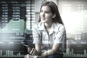 Business financial concept, Double exposure of Happy asian businesswoman sitting on working space and looking the Stock market exchange information and Trading graph in the modern Office