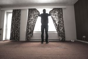 man closing curtains in empty home