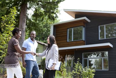 Real estate agent greeting couple at house