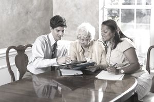 Senior woman getting advice on creating a POD account at dining room table with advisor and daughter-in-law.