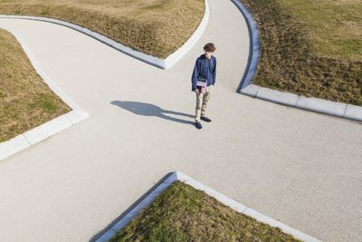 young man standing at a four-way crossroads trying to determine which way to go