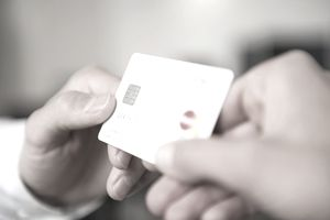 close up on a person's hand giving a credit card to another person's hand