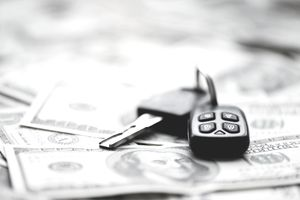 Set of car keys laying on a pile of money indicating the cost of car loan payments.