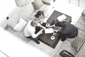 A couple sits across a coffee table from a man in a suit and they review a document.