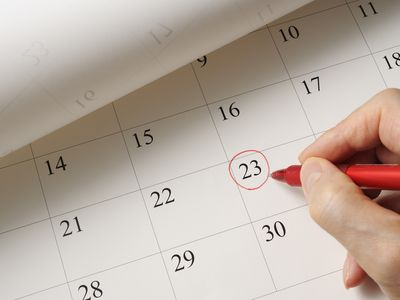 Person circling an important date on a calendar using a red pen