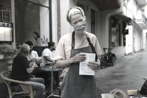 Waitress wearing face mask stands with back to a table of customers