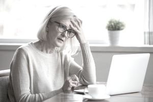 A concerned woman puts her hand to her forehead while looking at her laptop