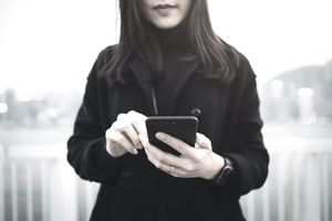 Young Woman With Face Obscured Holding Cell Phone and Using It Outside.