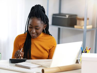 Close up of young woman at a home desk with a laptop and calculator