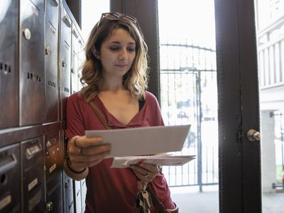 A young woman at an apartment's mailbox sorts through mail she received