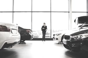 A woman looks around a showroom of new cars, thinking about which car to buy