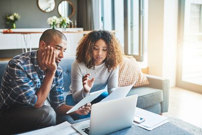 Shot of a young couple using a laptop and digital tablet while working on their home finances