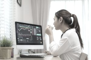 woman sitting at desk at home trading stocks or cryptocurrency